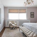 Rustikálna spálňa s čalúnenou lavicou, bielou šatníkovou skriňou na mieru, kresielkom a drevenou mriežkou skrývajúcou radiátor.