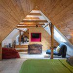 Podkrovie v tradičnej chalupe s dreveným obložením, so spálňou a miestnosťami na posedenie.
