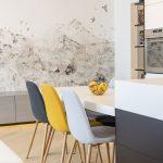 Moderný jedálenský stôl s čalúnenými stoličkami v sivej a žltej farbe.
