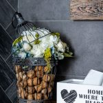 Dekorácia z kovovej nádoby s kvetinami a korkovými zátkami.