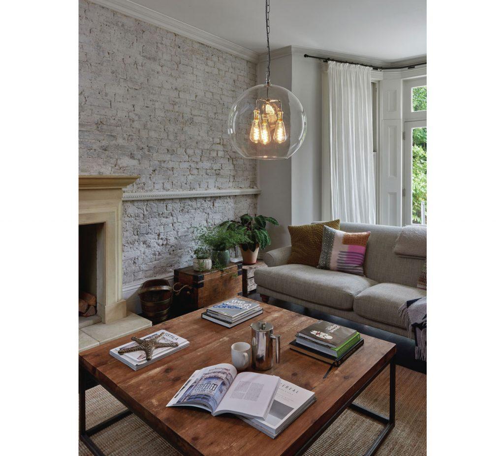 Úprava stien v obývačke: obývačka so sivou pohovkou, dreveným masívnym stolom, kozubom a tehlovou stenou namaľovanou na bielo.