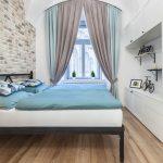 Spálňa s oblúkmi a tehlovou stenou, zariadená bielym nábytkom a pastelovými textíliami.