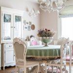 Rustikálna jedáleň s okrúhlym stolom so zeleným obrusom a starodávnou misou s kvetmi, s drevenými zdobenými stoličkami v bielej farbe a bielym príborníkom.