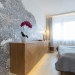 Moderná spálňa s čiernobielou tapetou s motívom stromov, so závesnou komodou, ktorá plynule prechádza do toaletného stolíka s čalúnenou taburetkou.