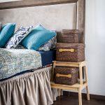Manželská posteľ s čalúneným čelom, vedľa postele je okerlík s pletenými úložnými krabicami.