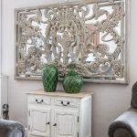 Interiér s rustikálnou bielou komodou, zelenými vázami a zrkadlom s dreveným vyrezávaným vzorom.