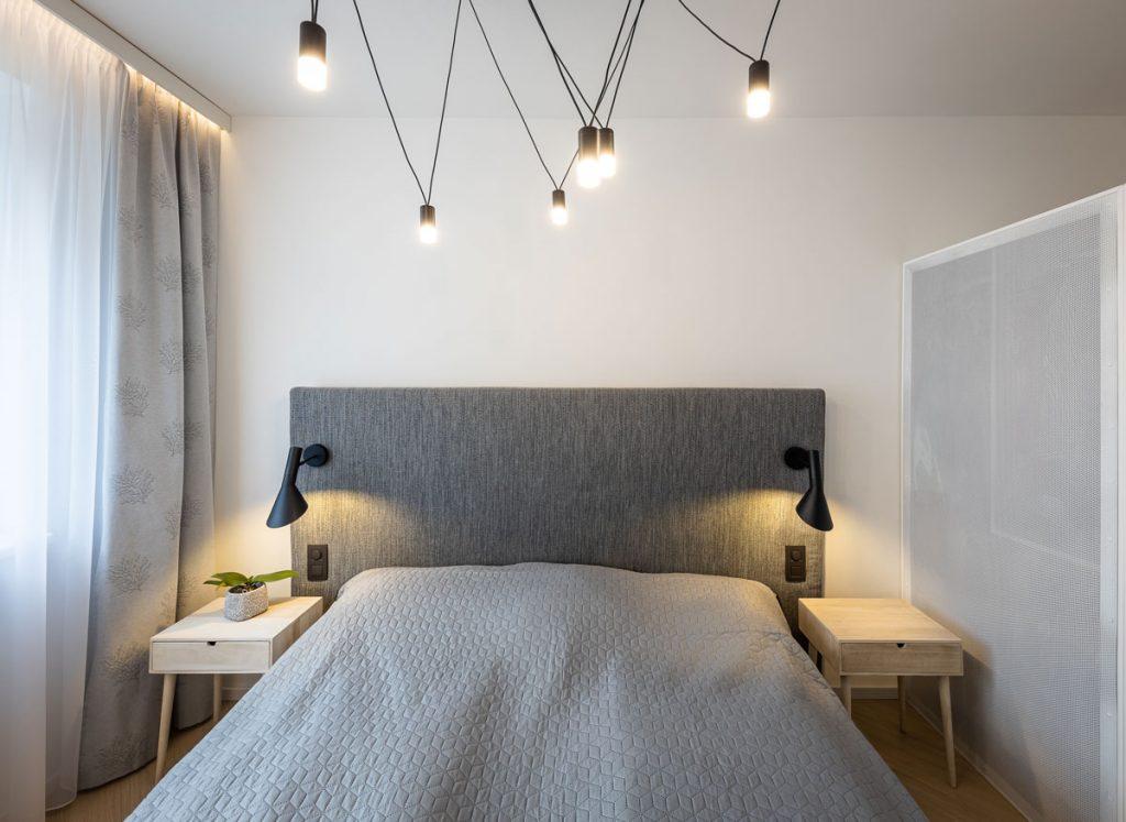 Moderná spálňa s posteľou s čalúneným čelom so zabudovanými svietidlami, s nočnými stolíkmi a šatníkom s perforovanou zadnou stenou.