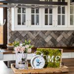 Kuchynská dekorácia z drevenej tácky, na ktorej je machový obraz s nápisom HOME, biely budík, sklenená nádoba a prútená nádoba s kvetmi.
