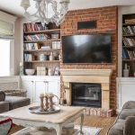 Obývačka vo vidieckom štýle s krbom s tehlovou stenou, knižnicou, bielou komodou, pohovkami a bielym zdobeným stolíkom.