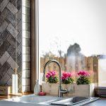Keramické kuchynské umývadlo s retro batériou situované pri okne.