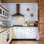 Vidiecka kuchyňa s bielou kuchynskou linkou a drevenými stropnými trámami.