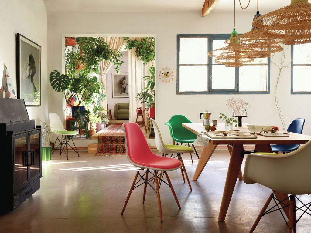 Retro interiér s jedálenským stolom a farebnými plastovými stoličkami na drevených nožičkách.
