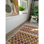 Farebný vzorovaný pletený koberček v interiéri.