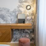 Spálňa s komodou, ktorá prechádza do toaletného stolíka, s čalúnenou taburetkou a tapetou s florálnym motívom.