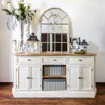 Stará biela komoda so striebornou vázou, lampášmi a vitrážovým zrkadlom.