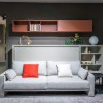 Obývačka a spálňa v jednom, riešená vyklápacou posteľou schovanou za pohovkou.