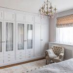 Vidiecka spálňa s bielou vstavanou skriňou so sklenenými výplňami a čalúneným kreslom.