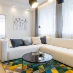 Moderná obývačka s bielou rozmernou sedačkou do L, farebným geometrickým kobercom, okrúhlym skleneným stolíkom a svietidlom v štýle reflektorov.