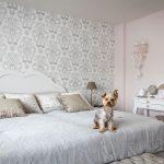 Spálňa vo vidieckom štýle s drevenou posteľou, bielym toaletným stolíkom a jemnou vzorovanou tapetou.