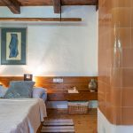 Spálňa v tradičnej chalupe s kachľovou pecou a dreveným stropom.