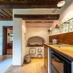 Zrekonštruovaná kuchyňa v tradičnej myjavskej chalupe s drevenými stropmi a výklenkom s murovanou pieckou.