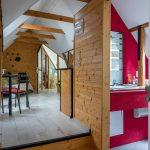 Zrekonštruované podkrovie s dreveným obložením a trámovými stropmi, s kuchyňou a kúpeľňou.