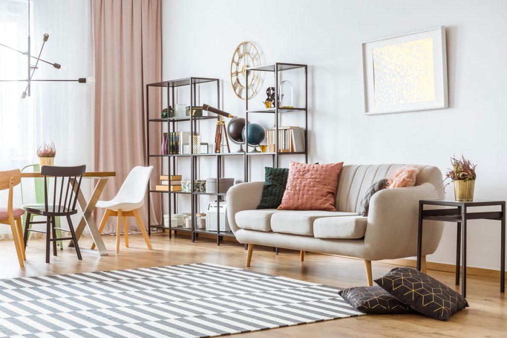Retro interiér s pohovkou na nožičkách, regálom, jedálenským stolom so stoličkami, pruhovaným kobercom a viacramenným svietidlom.