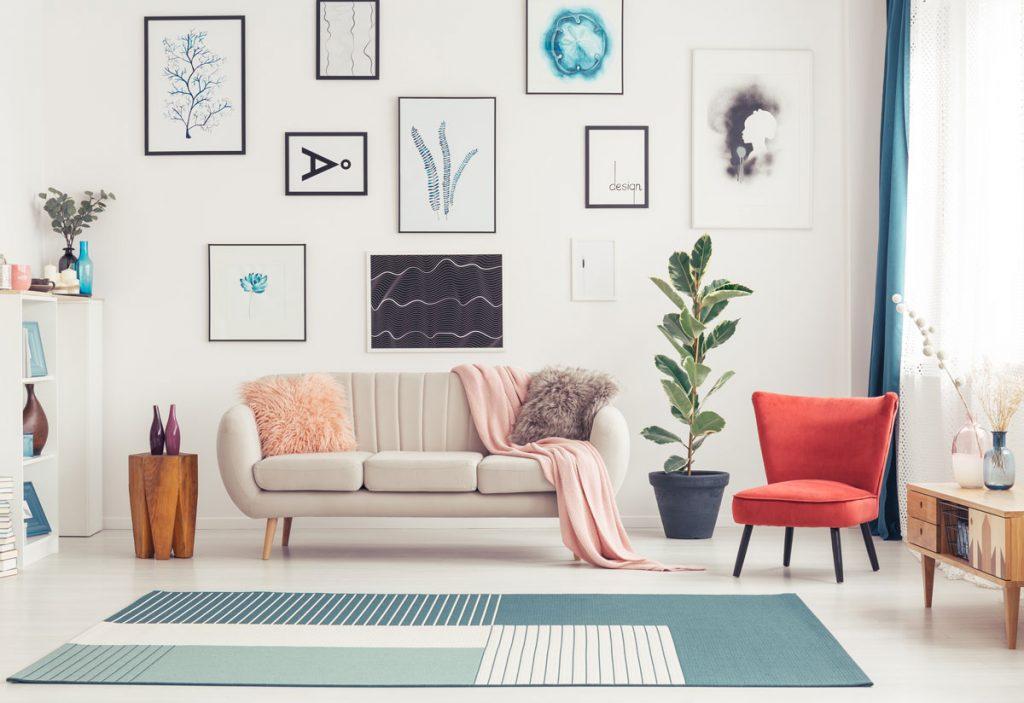 Úprava obývačkových stien: obývačka so sivou pohovkou, farebným kobercom, červeným kresielkom a obrazmi doladenými k interiéru.
