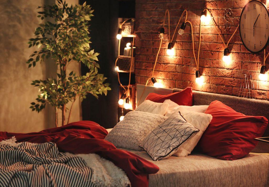 Spálňa s posteľou a s tehlovou stenou, na ktorej je naaranžovaná svetelná reťaz zo žiaroviek.