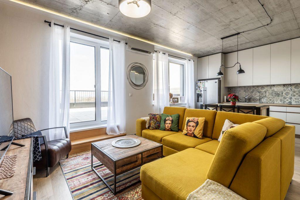 Priestor obývačky spojenej s kuchyňou v kombinácii industriálneho a rustikálneho štýlu, s priznaným betónovým stropom, výraznou žltou sedačkou a a vankúšmi s portrétom Fridy Kahlo.