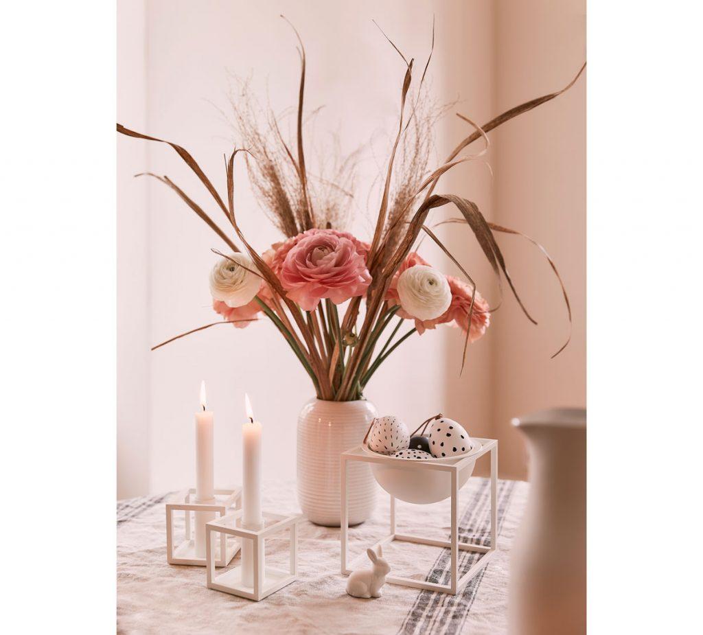 Veľkonočný aranžmán s vázou s kvetmi a stojanom, v ktorom sú uložené kraslice.