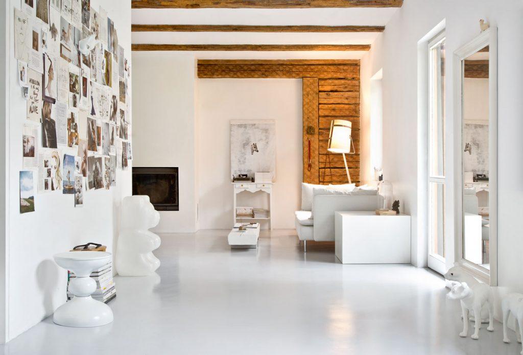 Moderný minimalistický interiér v tradične vyzerajúcej drevenici. S bielym nábytkom, kozubom, dizajnovými sochami, drevenými trámami a obložením.