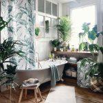 Kúpeľňa s vaňou na nožičkách, dreveným nábytkom a textíliami s kvetinovými motívmi, doplnená o živé rastliny.