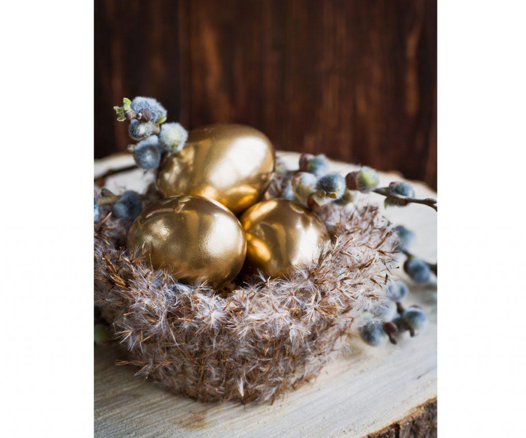 """Veľkonočná dekorácia zo zlatých vajíčok v """"hniezde"""" z pierok."""