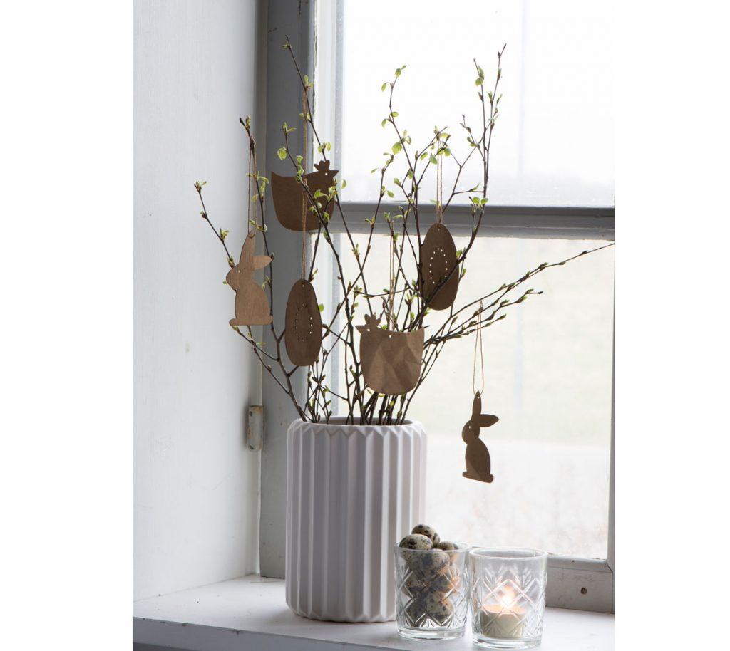Veľkonočná dekorácia v podobe bielej vázy s vetvičkami a papierovými závesnými zvieratkami.