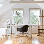 Minimalisticky zariadená pracovňa v podkroví drevenice, s bielym dizajnovým stolom, stoličkou a dreveným maliarskym stojanom.
