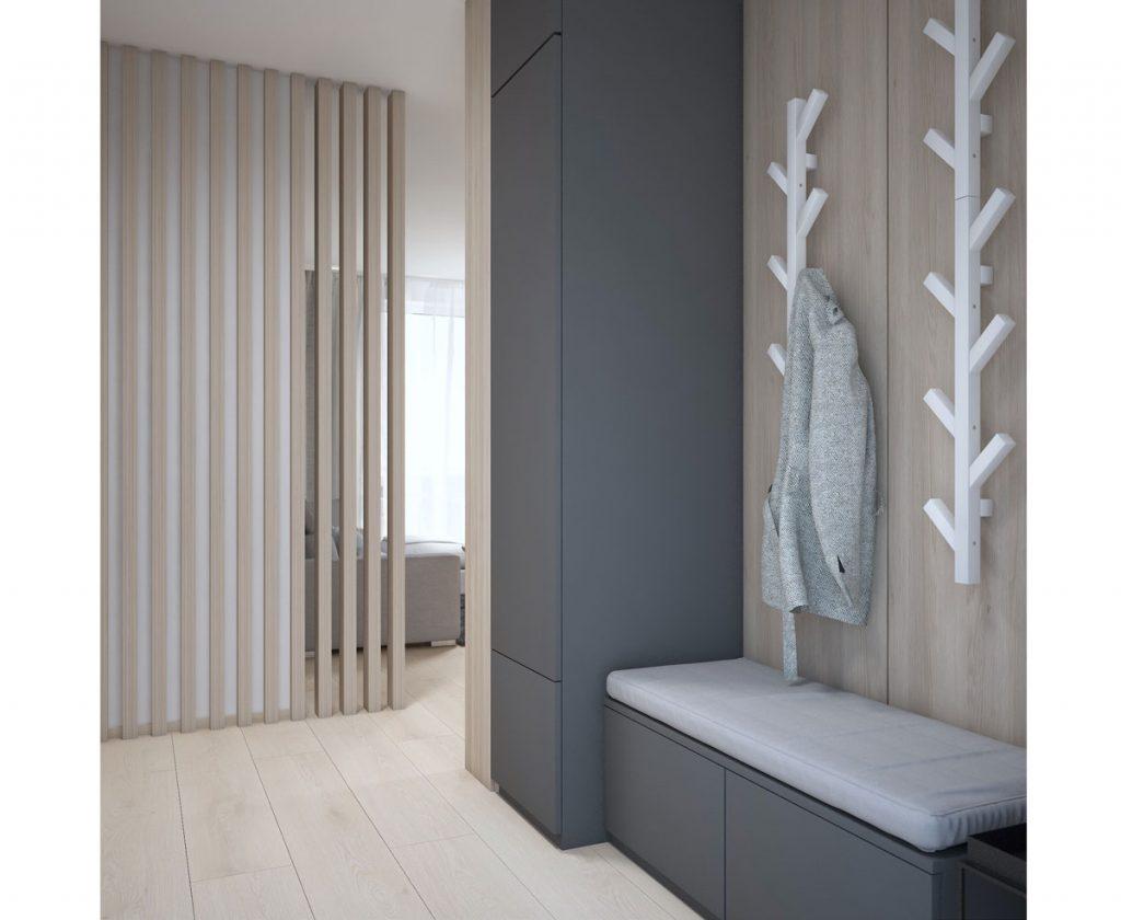 Malá chodba s úložnými priestormi na topánky a oblečenie, so sedením, vešiakom v tvare stromu a deliacim prvkom v podobe dreveného roštu.