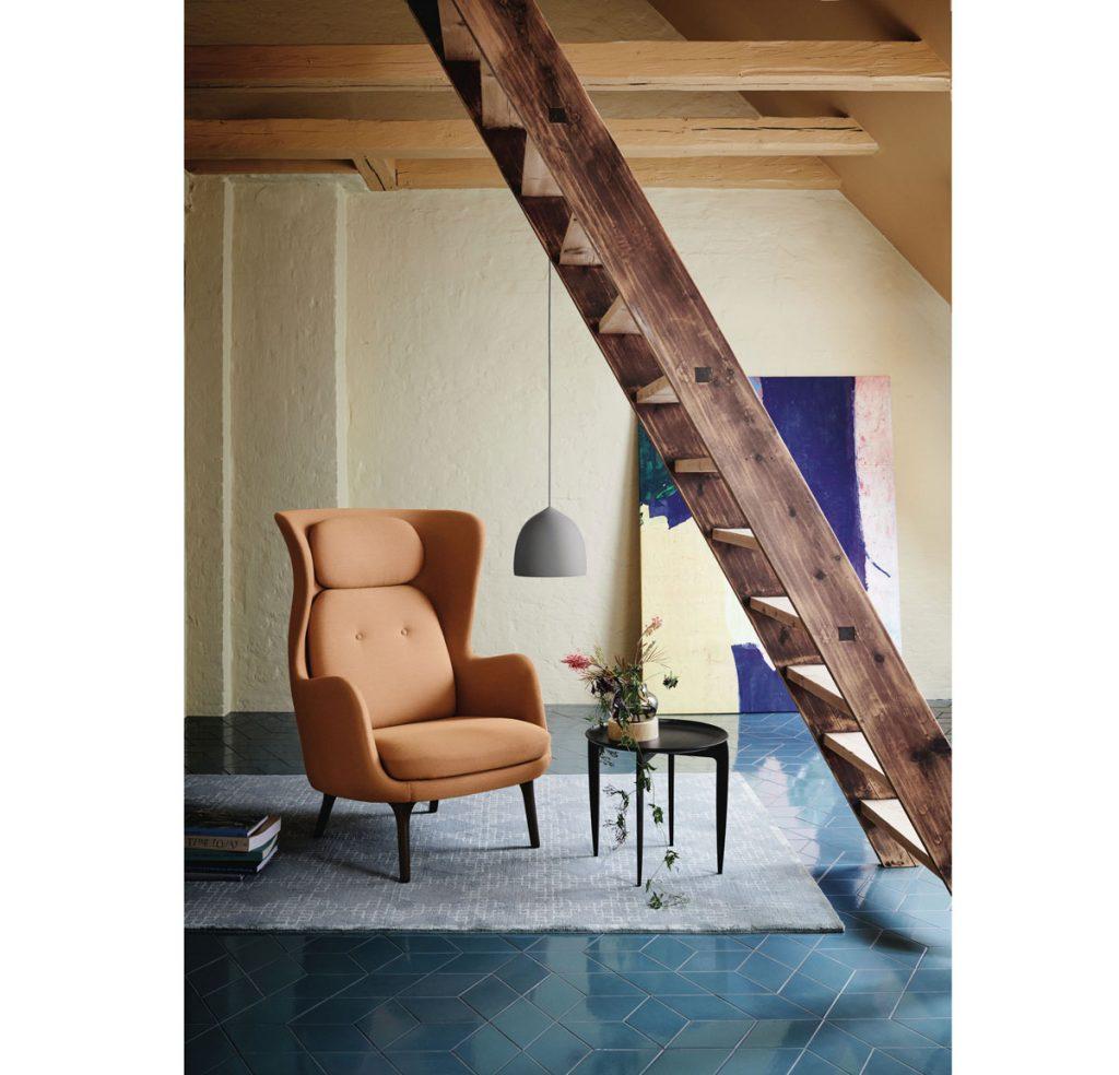 Interiér s kreslom v zemitom oranžovom odtieni v kontraste s modrou podlahou a kobercom.