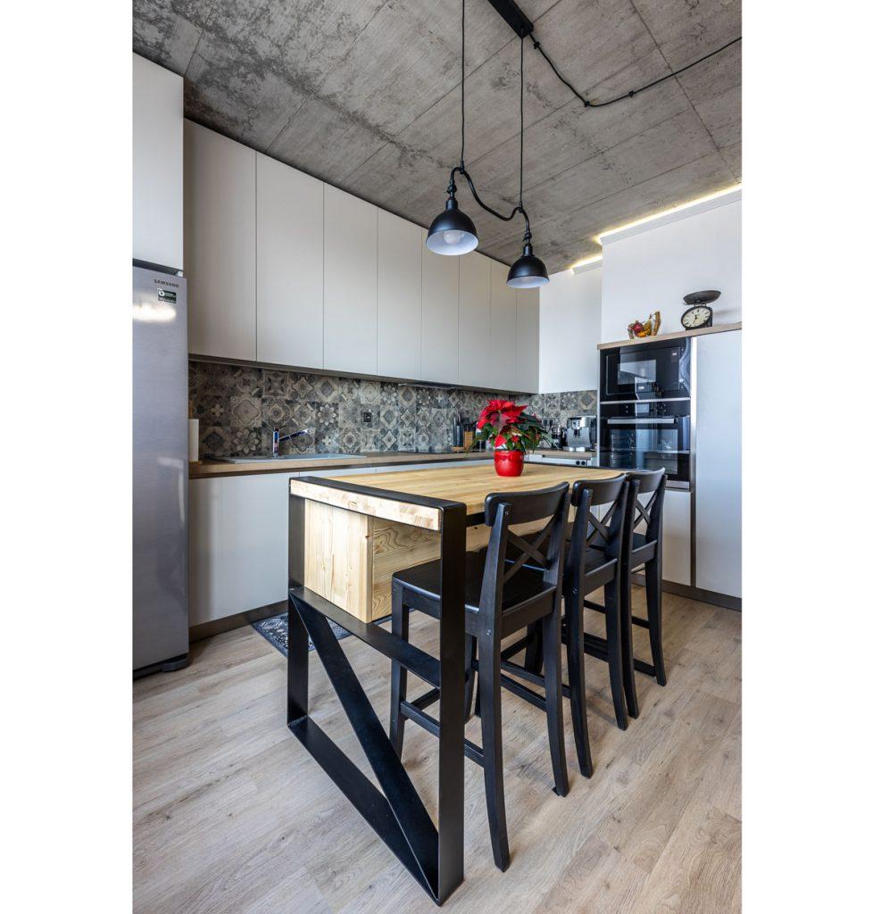 Kuchyňa v industriálnom štýle s bielou minimalistickou kuchynskou linkou, vzorovaným obkladom, kuchynským ostrovčekom z dreva a kovu a priznaným betónovým stropom.