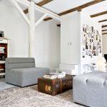 Obývačka v minimalistickom štýle so sivými kreslami, stolíkom zo starého lodného kufra, bielou otvorenou skrinkou na kolieskach a skrytým schodiskom v deliacej stene.
