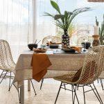 Jedálenský stôl ladený v prírodnom štýle s jutovým obrusom a vypletanými stoličkami .