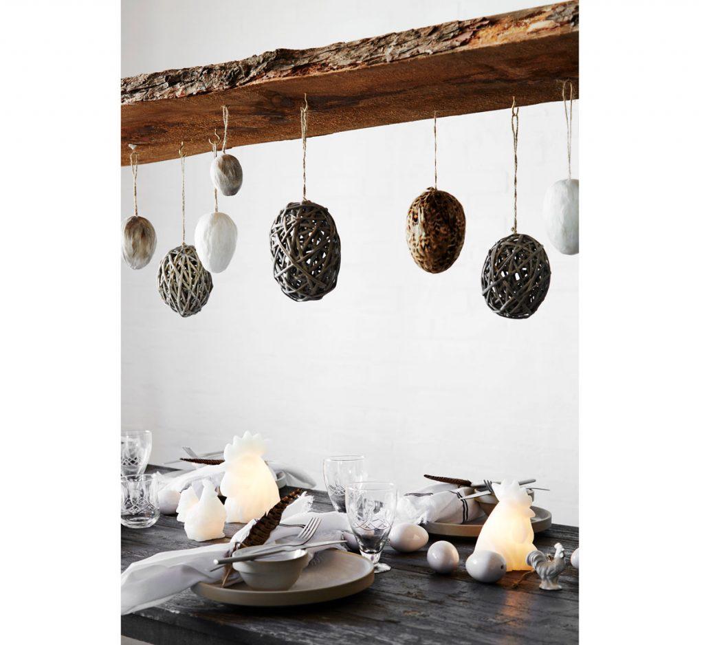 Veľkonočná dekorácia z prírodného materiálu v podobe vajíčok zavesených z dreveného trámu.