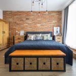Spálňa v industriálnom štýle s posteľou, lavicou s úložnými boxami, textíliami s Fridou Kahlo a tehlovou stenou.