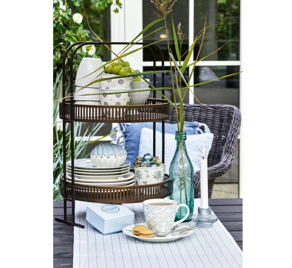 Veľkonočné jarné stolovanie s etažérom, farebnou sklenenou fľašou s kvetinou a riadmi.