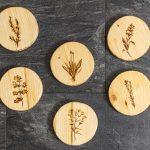 Rozhovor so ChopperArt: drevené okrúhle podložky pod šálky s gravírovaným vzorom byliniek.