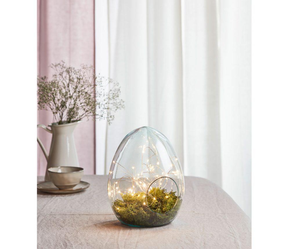 Veľkonočný aranžmán zo sklenenej nádoby v podobe vajíčka, v ktorej je mach a svetielka.