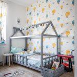 Detská izba s tapetou so vzorom teplovzdušných balónov a posteľou v tvare domčeka.