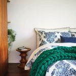 Posteľ s obliečkami s folklórnym vzorom a zelenou pletenou dekou.