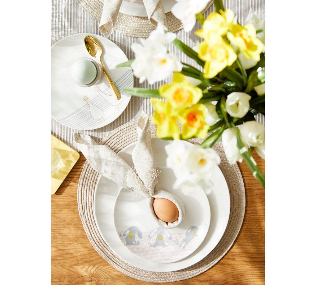 Veľkonočne prestretý stôl s taniermi so symbolmi jari a vajíčkom so servítkou upravenou na zajačika.