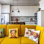 Obývačka prepojená s kuchyňou so žltým gaučom, motívmi Fridy Kahlo a industriálnymi prvkami.